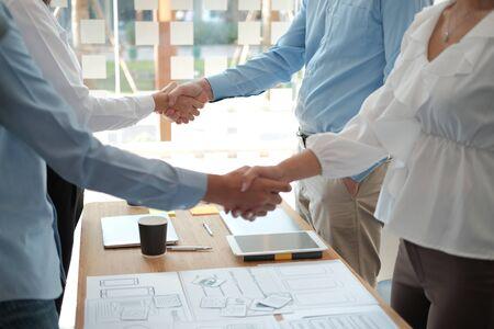 businessman shaking hands with businesswoman after UI UX desiner meeting. Business people handshaking. Greeting deal, teamwork partnership concept. Reklamní fotografie - 135128637