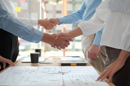 businessman shaking hands with businesswoman after UI UX desiner meeting. Business people handshaking. Greeting deal, teamwork partnership concept.