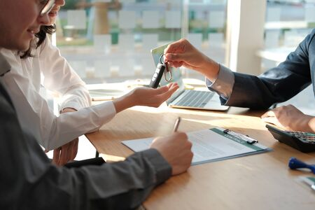 dealer salesman giving car key to new owner. client signing insurance document or rental car lease form