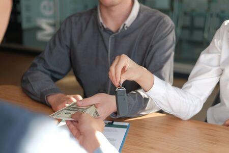 client pay for new car. salesman dealer giving key to owner. car sale & dealership in auto business Reklamní fotografie - 135129056
