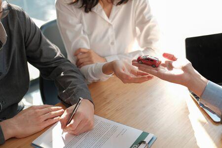 dealer salesman giving car to new owner. client signing insurance document or rental car lease form Reklamní fotografie