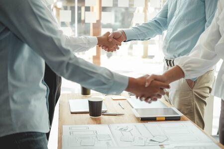 businessman shaking hands with businesswoman after UI UX desiner meeting. Business people handshaking. Greeting deal, teamwork partnership concept. Reklamní fotografie - 135128850