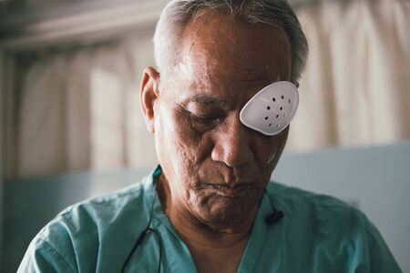 patient covering eye with protective shield & medical plaster after eyes cataract surgery in hospital Banco de Imagens