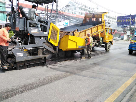 Chiang Mai, Thailand - October 28, 2020: workers laying hot asphalt concrete for repairing road