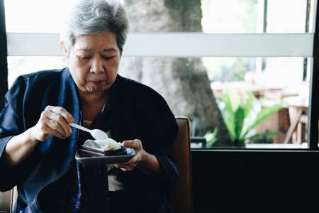 old asian elderly senior elder woman eating cheesecake at restaurant. mature retirement lifestyle