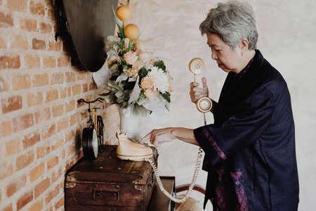 old asian elderly senior elder woman dialing telephone number at home