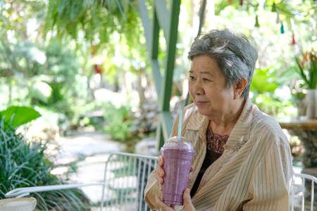 old asian elderly senior elder woman drinking berry smoothie yogurt milkshake at restaurant. mature retirement lifestyle
