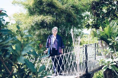 elder woman resting in garden. asian elderly female relaxing outdoors. senior leisure lifestyle
