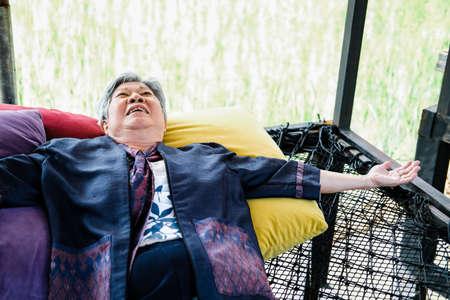 asian elderly woman elder  lying resting relaxing outdoors. senior leisure lifestyle