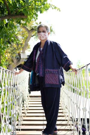 asian elderly woman elder wearing facial mask resting relaxing outdoors. senior leisure lifestyle