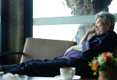 asian elder female woman resting relaxing on sofa at home. elderly senior leisure lifestyle
