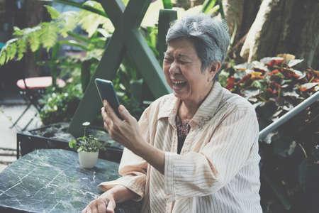 asian old asian elderly senior elder woman talking on video call on smart mobile phone Stock Photo