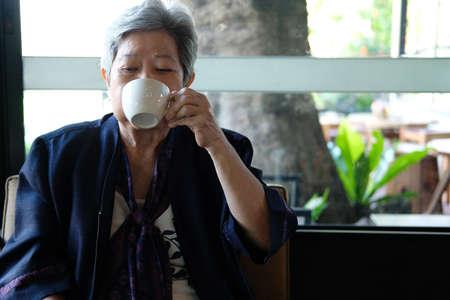 old elderly senior elder woman drinking hot mocha coffee tea at restaurant. mature retirement lifestyle Stock Photo