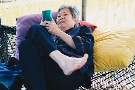 asian elder senior woman using mobile smart phone. elderly female holding cellphone. mature retirement lifestyle
