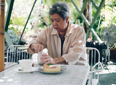 old elderly senior elder woman  taking sugar for coffee at home. mature retirement lifestyle