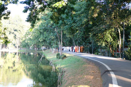Chiang Mai, Thailand -  November 19, 2020: buddhist monk and people walking for mindfulness meditation at Chiang Mai university in Chiang Mai, Thailand on November 19, 2020