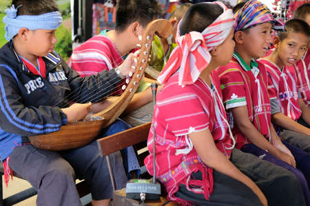 Chiang Mai, Thailand - December 23, 2020: Karen hill tribe in northern thailand singing and playing music for entertaining buyers in Chaodoi market in Chiang Mai, Thailand on December 23, 2020. Redakční