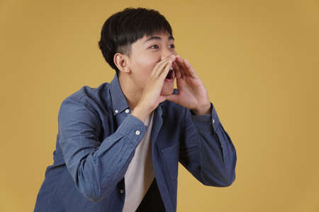 portrait of excited young asian man dressed casually with shouting announcing holding hands near mouth isolated on yellow studio background