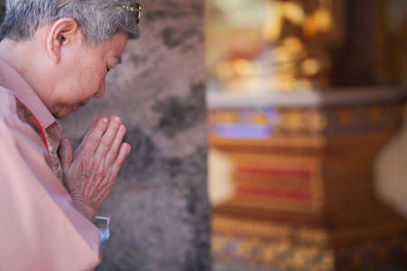 old asian elder senior woman traveler tourist praying at buddhist temple.