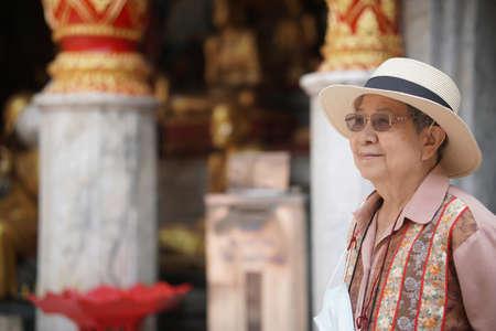 old elderly female elder woman traveller traveling in asian temple. senior leisure lifestyle