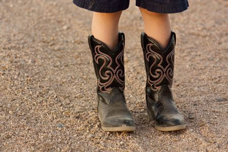 A kids boots, standing on the gravel photo