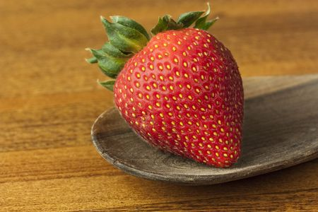 A single strawberry on an old wooden spoon