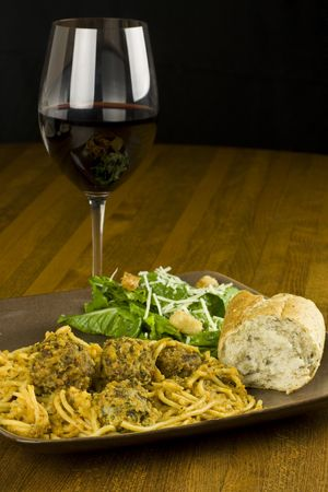 A plate of spaghetti with meatballs and a side salad with red wine. photo