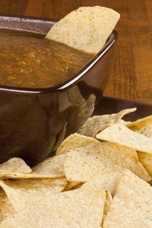 corn tortilla: Corn tortilla chips around a brown bowl of homemade salsa
