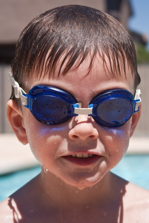 cousin: Boy smiling by the pool while wearing swimming goggles Stock Photo