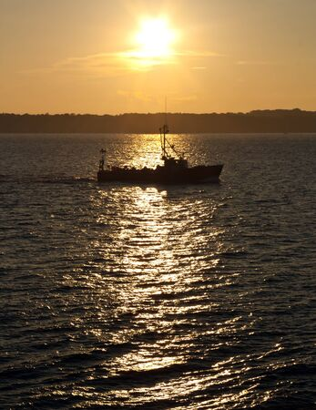commercial fishing: Commercial fishing boat silhouetted at sunset Stock Photo
