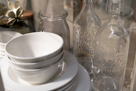 ware: stack of white ceramic bowl, plate and bottles