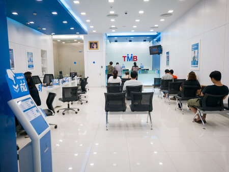 Chonburi, Thailand, July 2017: Bank counter service and people waiting for financial transaction in the bank Redactioneel