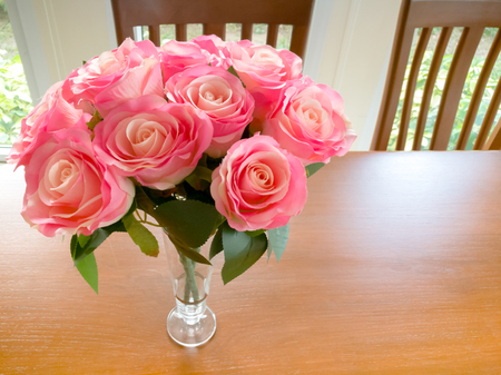 luxury pink rose on the wooden din table Stock Photo