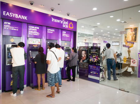 Chonburi, Thailand, July 2017: people standing in queue for using ATMs