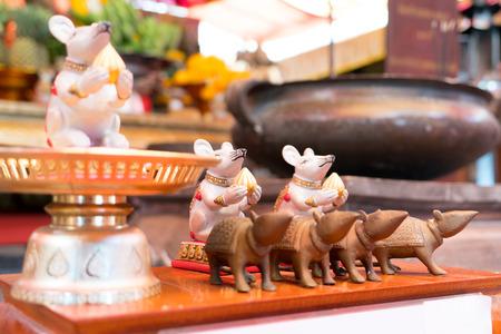 神社のテーブルの上の小さな白と茶色のネズミの像