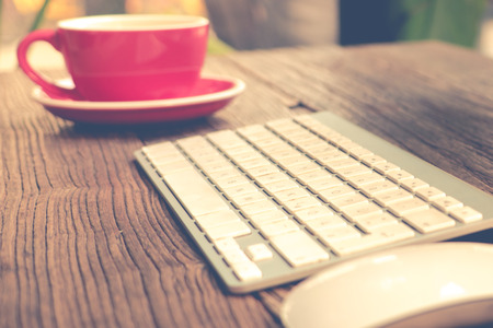 focus on English alphabet of the white keyboard with mouse and red cup of coffee