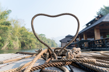 closeup thick rope tie the heart shape on the wooden terrace near river