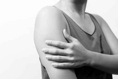 closeup women arm and shoulder paininjury with white backgrounds, healthcare and medical concept - B&W filter