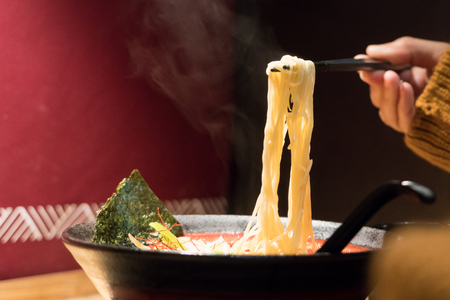noodle ramen on chopstick hold on women hand, food and drink concpet with copy space