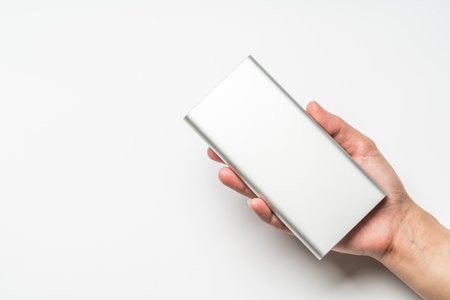 white silver power bank on hand isolate. save energy and reduce energy efficiency concept