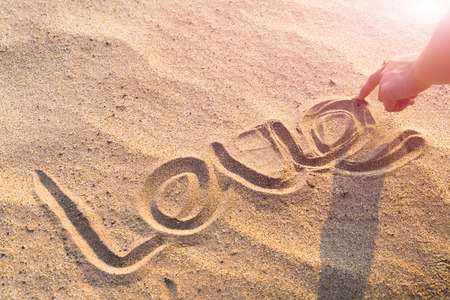 LOVE word writing on the white sand nature on the beach. summer trip Banco de Imagens