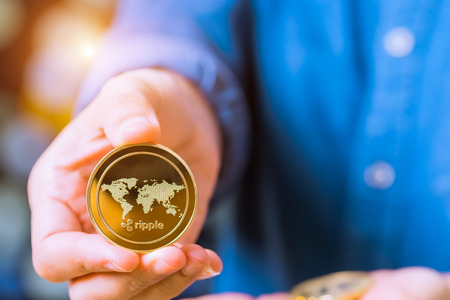 cryptocurrency coins - Ethereum, Litecoin, Bitcoin, Ripple. Women hold the cryptocurrency coin on hand. Physical bitcoins gold and silver coins Stock Photo - 100598160