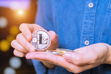 cryptocurrency coins - Litecoin, Ethereum, Bitcoin, Ripple. Women hold the cryptocurrency coin on hand. Physical bitcoins gold and silver coins