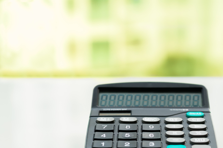 Calculator on the white table near window, closeup sideview isolated Stock Photo
