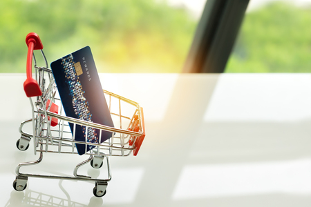 credit card on shopping cart trolley on white table with green backgrounds Stock Photo