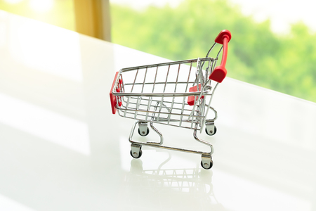 Empty shopping cart trolley on white table with green backgrounds