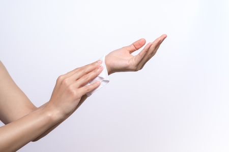 Woman cleaning her hands with white soft tissue paper. isolated on a white backgrounds 版權商用圖片