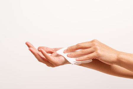 Woman cleaning her hands with white soft tissue paper. isolated on a white backgrounds 免版税图像