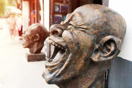 Cabeza de estatuas de bronce de la risa, escultura de cabeza divertida Foto de archivo