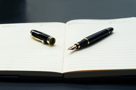 Opened lined diary notebook with a luxury pen with copy space